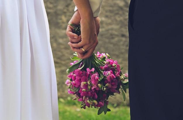 Свадебная пара держит в руках фиолетовый букет. романтическое летнее фото влюбленных жениха и невесты. ярко-зеленая трава и каменная стена. обручальные кольца и клубок рук.
