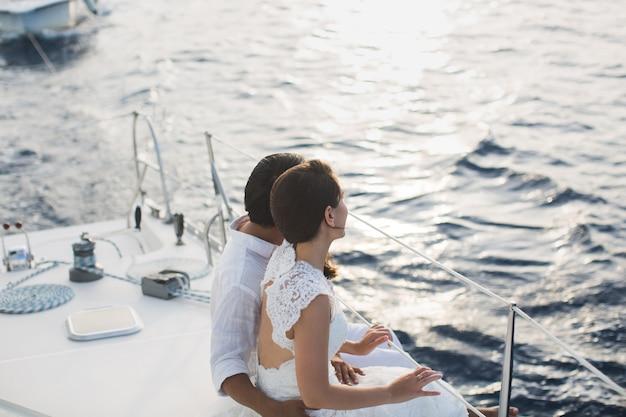 結婚式のカップルがヨットで抱いています。新郎と美しさの花嫁。