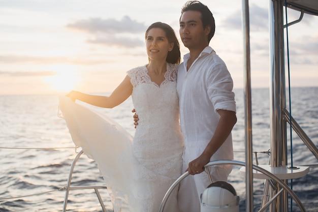 Свадебная пара обнимается на яхте. невеста красоты с женихом.