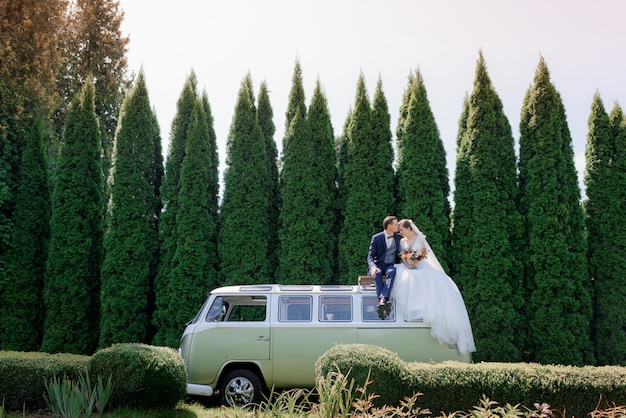 Wedding couple is sitting on the roof of green minivan outdoors surrounded with green trees