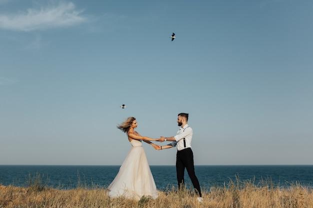 결혼식 한 쌍은 바다 해변에서 돌고있다.