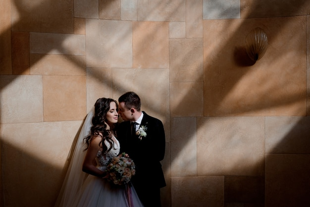 Wedding couple is standing near the wall in sun rays and almost kissing, marriage concept