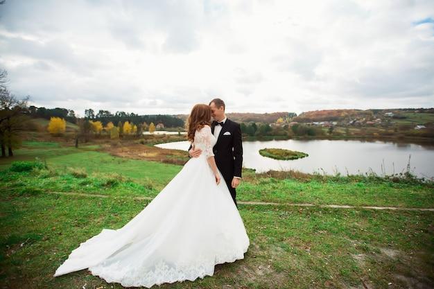 Свадьба, пара поцелуев в холмах у реки на закате. ветер развевается над длинной завесой. пейзаж холмов и гор