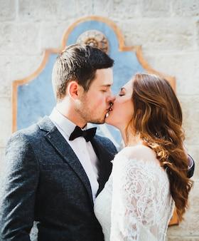 旧市街で結婚式のカップルのキス。背景に古代の町の石の壁。髪を下にした素朴なレースの花嫁と灰色のスーツと蝶ネクタイの新郎。ヴィンテージな雰囲気の通りでロマンチックな愛。