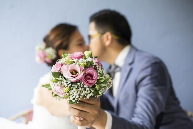 Свадебная пара целуется и держит цветок в камеру.