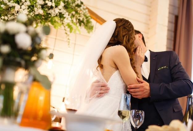 装飾されたレストランのテーブルでキスする結婚式のカップルはロマンチックなmonent結婚式の日をクローズアップ