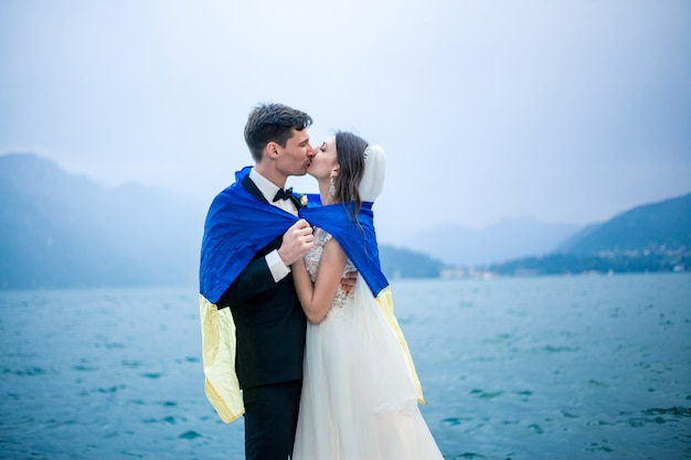 Wedding couple kissing on the background of a lake and mountains