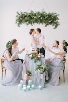 Wedding couple kissing at the decorated wedding table with their bridesmaids and groomsmen