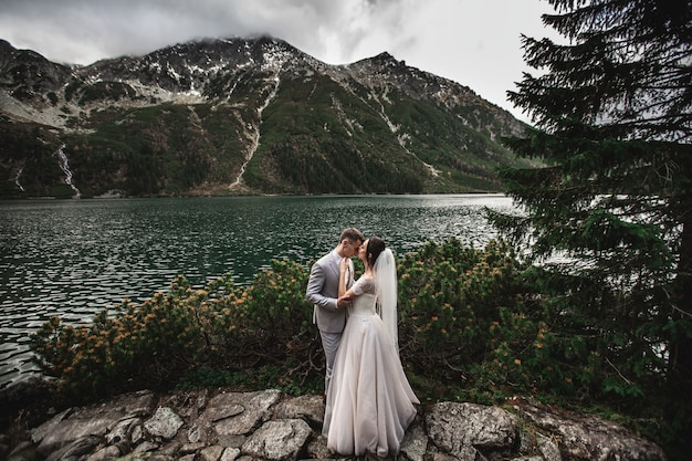 Wedding couple kissing near the lake in tatra mountains in poland, morskie oko