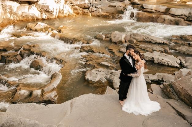 結婚式のカップル、石の川を背景に恋人たち。