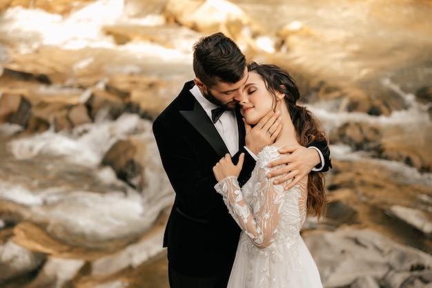 Свадебная пара, влюбленные на фоне каменной реки.