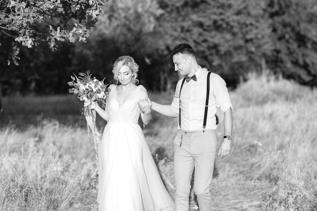 Wedding couple on the nature in summer day. the bride and groom hugging at the wedding. black and white photo