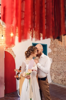 Wedding couple near photo zone in form of an arch with flowers