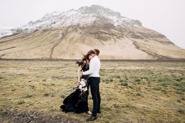 Свадебная пара на фоне заснеженных гор обнимаются невеста в черном платье и жених