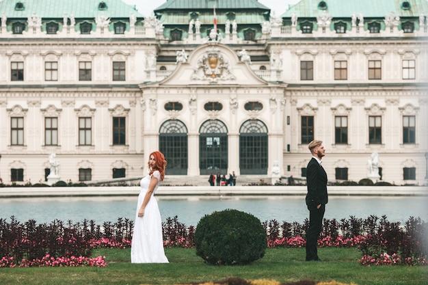 ウィーンのベルヴェデーレの不動産で散歩中の結婚式のカップル