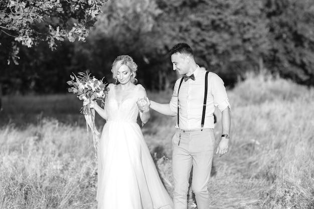 Свадебная пара на природе в летний день. жених и невеста обнимаются на свадьбе. черно-белое фото
