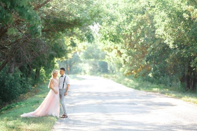 Свадебная пара на природе в летний день. жених и невеста обнимаются на свадьбе. вместе навсегда