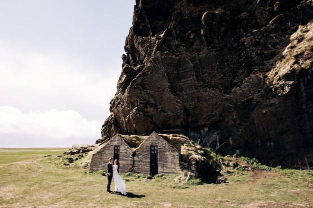 Свадебная пара позирует у старых домов, покрытых мхом, на фоне скалистой горы