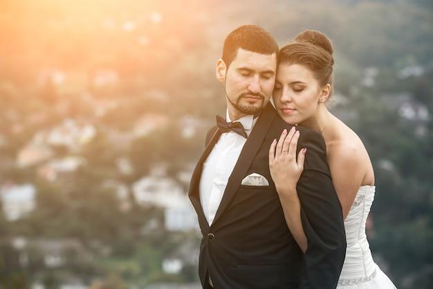 Sposi in posa per la fotocamera sulla gobba