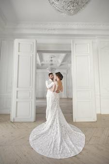 Свадебная пара позирует в белой комнате