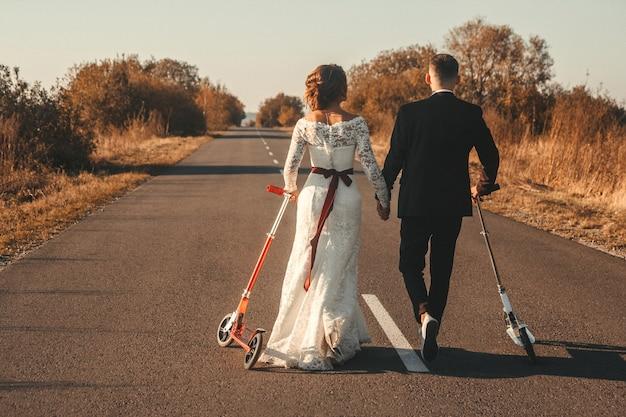 日没時に街の外の道路に沿ってスクーターに乗って結婚式のカップル。