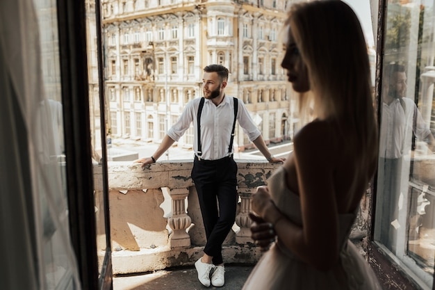 Wedding couple stand on a hotel balcony with beautiful architecture on surface, view through an open antique window.
