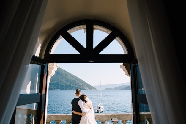 Wedding couple stand on a hotel balcony with sea view view through an open antique window fineart