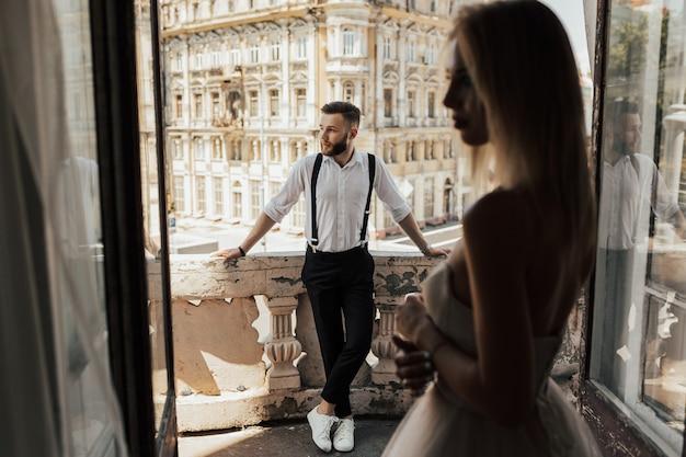 結婚式のカップルは、表面に美しい建築物があるホテルのバルコニーに立って、開いたアンティークの窓から眺めます。