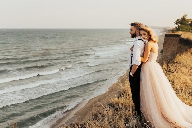 海の表面に対して崖の上に立っている結婚式のカップル。