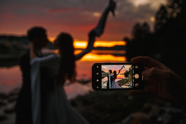 A wedding couple standing next to a river. in the background, the village at sunset, shooting on the phone