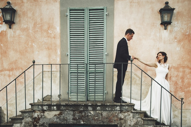 Wedding couple stands on the footsteps before an orange italian villa