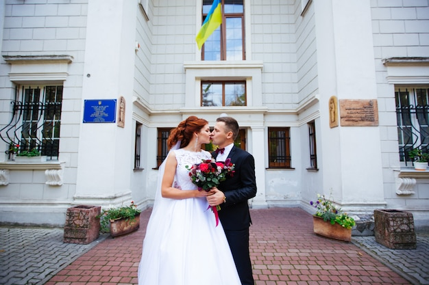 Wedding couple stands near registry office, wedding day