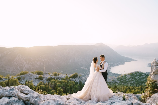A wedding couple stands on top of a mountain with panoramic views of the bay of kotor at sunset the