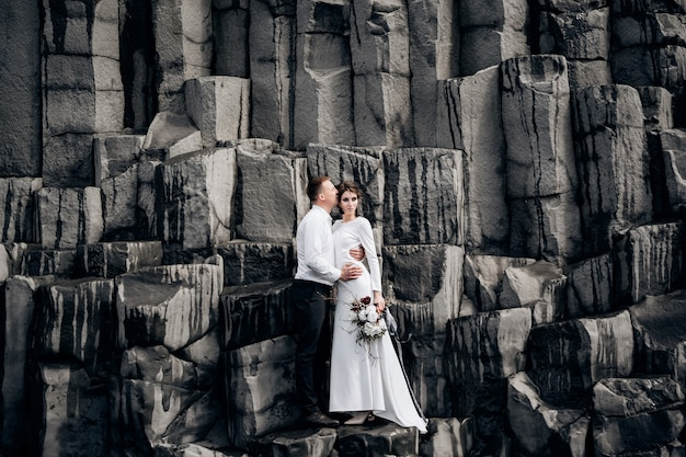 A wedding couple stands on a wall of stone pillars. the bride and groom are hugging on basalt kekurs, on the black sandy beach of vik. destination iceland wedding.