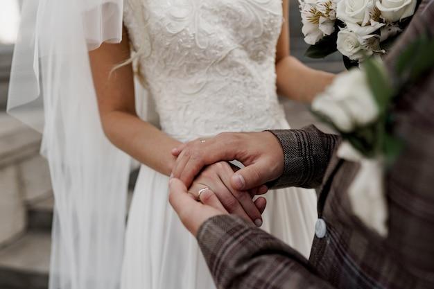 結婚式のカップルは、お互いに手で触れます。愛と優しさ。