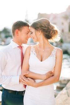 Свадебная пара касается лба друг друга крупным планом