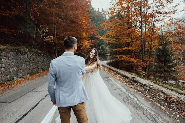 山の道を歩いて手をつないで結婚式のカップル