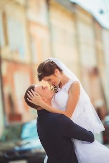 都市の風景の中を元気に歩く結婚式のカップル。新郎新婦の抱擁とキス。愛の人々。街の通り。結婚式の日。水平カラー写真。