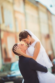 Wedding couple walking cheerfully in urban landscape. bride and groom embracing and kissing. people in love. city streets. wedding day. horizontal color photo.