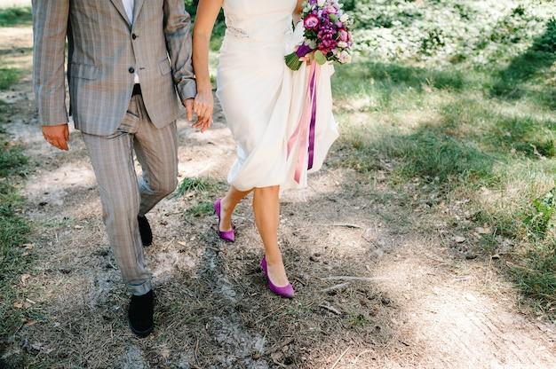 Свадебная пара, прогулки на природе. невеста в платье и жених идут в зеленый сад, поле и держат в руках свадебный букет цветов и зелени. вид спереди вниз.