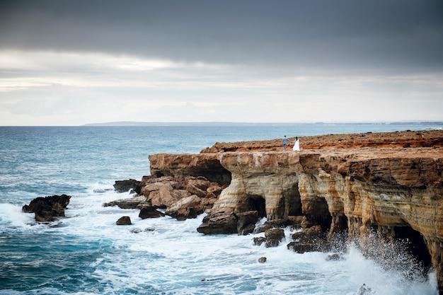 キプロスの海沿いの岩の上を歩く結婚式のカップル