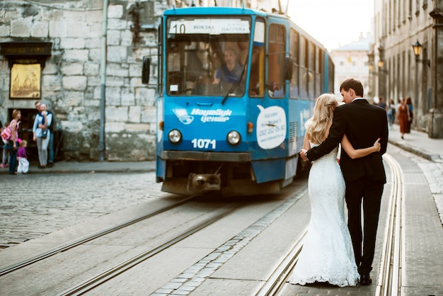 Wedding couple walking on tram ways