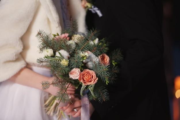 美しい花束のクローズアップと結婚式のカップル