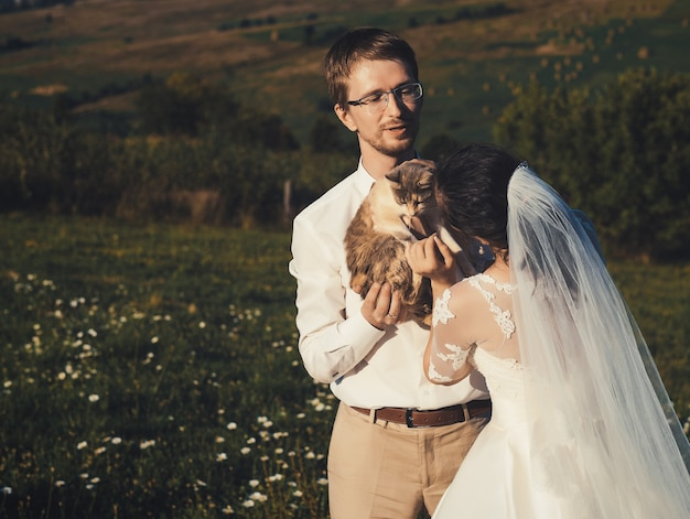 Wedding couple with cat  of carpathian mountain