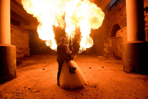 Wedding couple with skull face art is standing in the dark