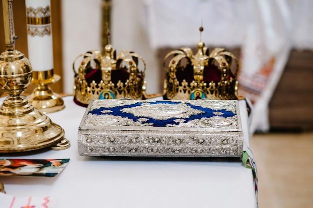 Свадебные короны и библия. свадебная корона в церкви готова к церемонии бракосочетания. крупным планом. божественная литургия.