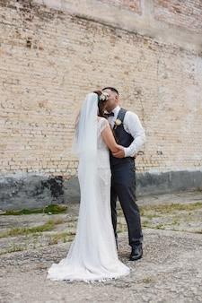 長い白いドレスを着た結婚式の日の花嫁は、レンガの壁のカップルの近くで屋外で抱き合ったりキスしたりする新郎