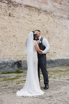 Wedding day bride in long white dress ang groom hugging and kissing outdoors near brick wall coupl