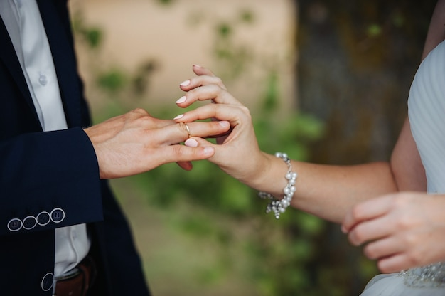On the wedding day, the bride puts an engagement ring on the groom's finger.