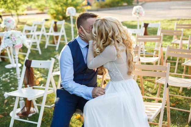 День свадьбы. молодожены целуются на церемонии бракосочетания. страстные объятия влюбленной пары на месте свадебного торжества. свадебный романтический момент на праздничной вечеринке крупным планом. романтическое свидание на природе.